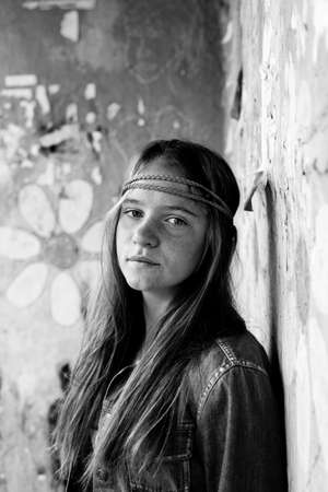 Portrait of young cute girl hippie, dirty background. Black and white photo.