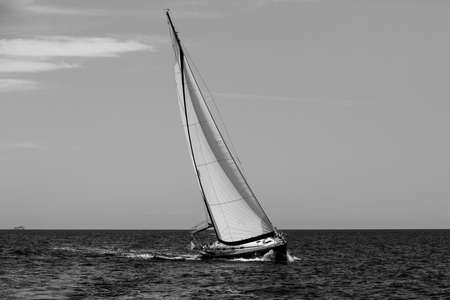 Luxury yachts. Sailing in the wind through the waves at the Aegean Sea. Black and white photo.