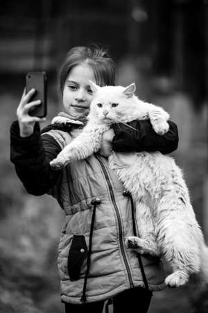 Little cute girl selfie with a stray cat on the phone. Black and white photo.