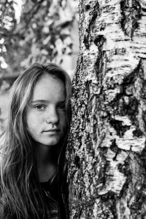 Pretty girl in the birch forest. Black and white photo.