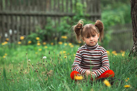 Little cute girl posing for the camera outdoor in the park. Stockfoto