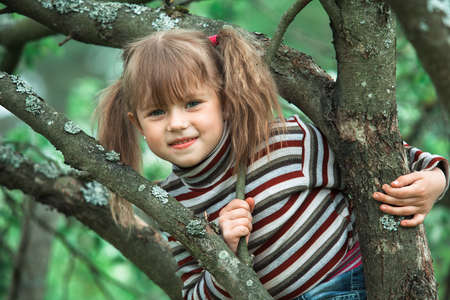 Portrait of little girl sitting on a tree in the garden.