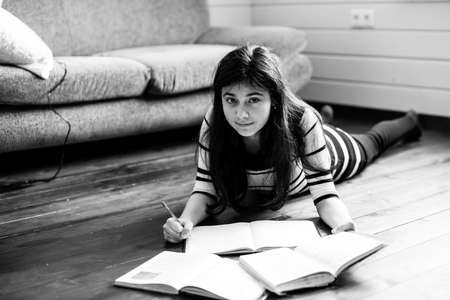 Teengirl doing homework lying on the floor in the room. Black and white photography.