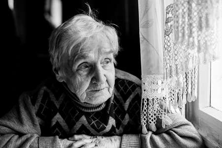 An old woman looking out the window. Black-and-white photography.