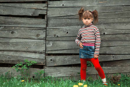 Cute five-year girl posing for the camera outdoor near wooden wall in the village. Stockfoto