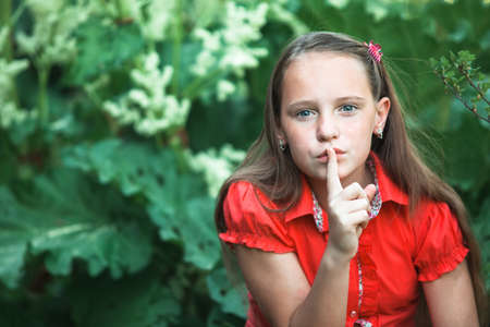 Teen young girl with her finger over her mouth, hushing.