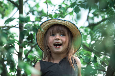 Little cute funny girl in a straw hat in the park. Stockfoto