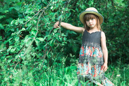 Little lovely girl in a straw hat in the park. Stockfoto