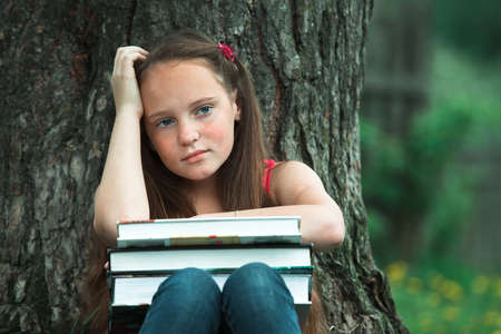 Tired teen girl with books in the park. Stockfoto