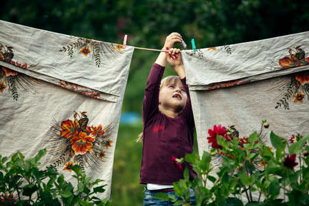 Little cute funny girl with clothespin and the clothesline. Stockfoto