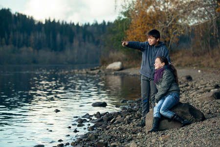 Couple of teenagers romantically a date near the river. Nord of Russia.