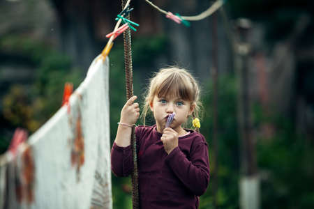 Little cute girl with clothespin in the village.