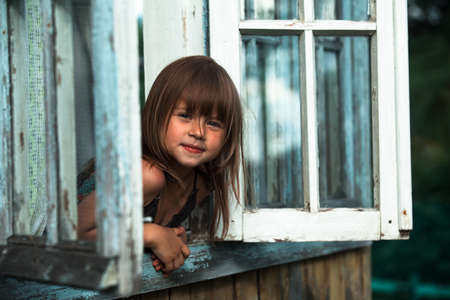 Little cute girl looks out the window rural house.
