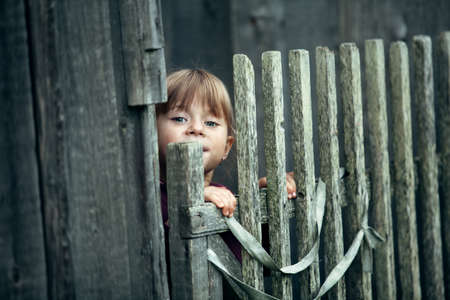 Little cute funny girl near vintage rural fence.