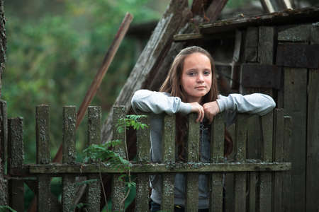 Teengirl standing near vintage rural fence in the village. Stockfoto
