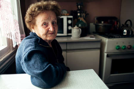 An old woman pensioner sitting in the kitchen.