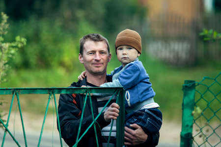 A man holds his young son in his arms, outdoors. Stockfoto