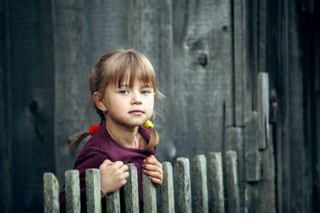 Portrait of little cute girl near vintage rural fence.