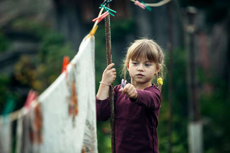 Little cute girl with clothespin outdoor in the village.
