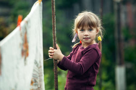 Lovely little girl with clothespin, outdoor