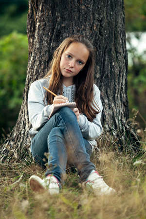 Teen girl writing in a notebook while sitting in the park.