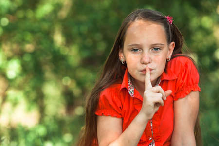 Hushing. Teen girl with her finger over her mouth. Stockfoto