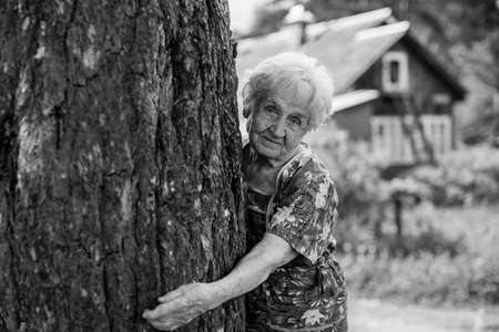 Old woman hugging a tree in the village. Black and white photo. Stockfoto