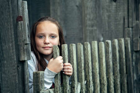 Portrait of teen girl over vintage rural fence.