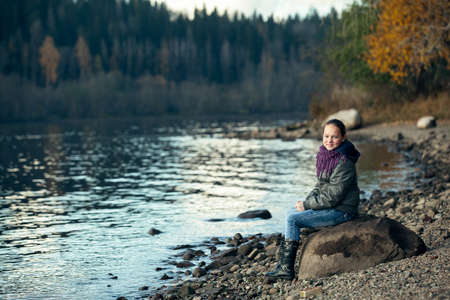 A teenage girl sits on a rock on the Bank of the river. Stockfoto
