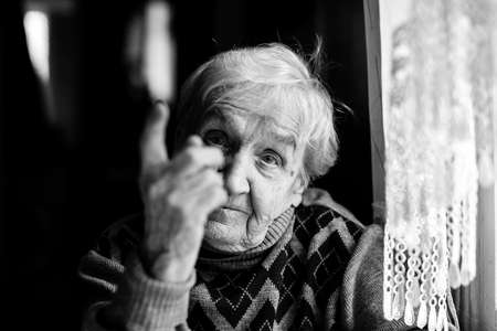 An elderly woman threatens with a finger looking at the camera. Black and white photography. Banco de Imagens