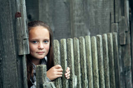 Portrait of teengirl standing near vintage rural fence