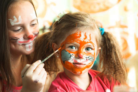 Two sisters playing with artistic painting face.