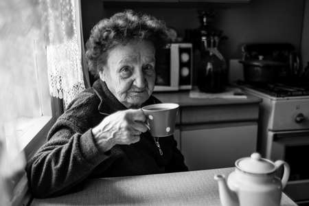 An old woman drinking tea in the kitchen. Black and white photography.