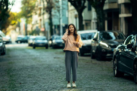 Young woman standing in the middle of the street.