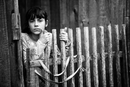 Teen girl standing near rural fence. Black and white photography. Reklamní fotografie