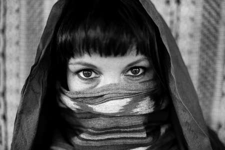 Close-up portrait of a woman covering her face with a veil. Black and white photography. Stock Photo