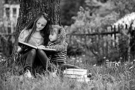 Children sisters reading the book in the summer park. Black and white photography.