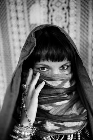 Portrait of a woman covering her face with a veil. Black and white photography.