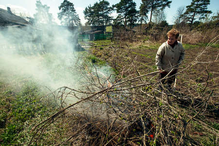 Old woman cleans and burns branches on her farm.