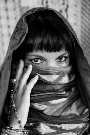 Portrait of a woman covering her face with a veil. Black and white photo.