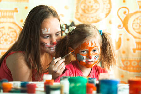 Two little cute sisters playing with face painting in the home.