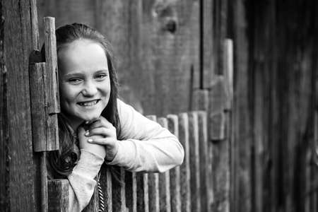 Portrait of teengirl standing near vintage rural fence, black-and-white photo.