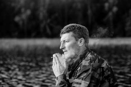 Fisherman in camouflage smoking a cigarette on a rubber boat in the lake. Black and white photo.