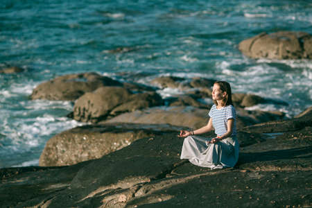 Young yoga woman meditates in the lotus position sitting on rocks on the ocean coast.