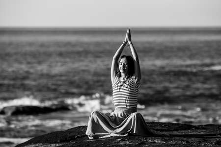 A young yoga woman meditates in the lotus position sitting on rocks on the Alantic ocean coast. Black and white photo.