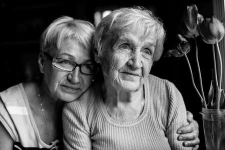 An old woman hug with her adult daughter. Black and white portrait.
