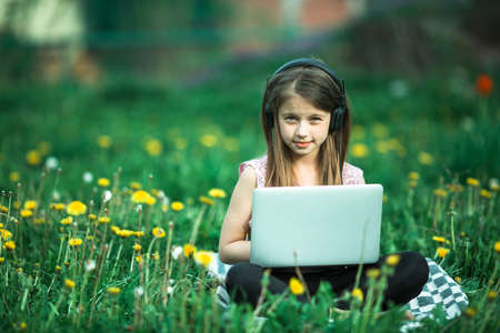 Little girl with laptop lying on the green grass at summer.