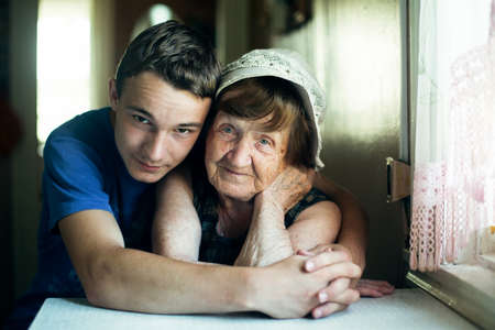 An old woman and her grandson portrait together in an embrace.