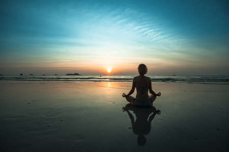 A woman sitting on beach during sunset and meditating at yoga pose.