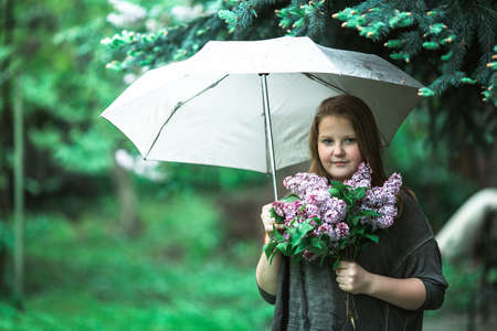 Teengirl with a bouquet of lilacs standing under an umbrella in the green garden.